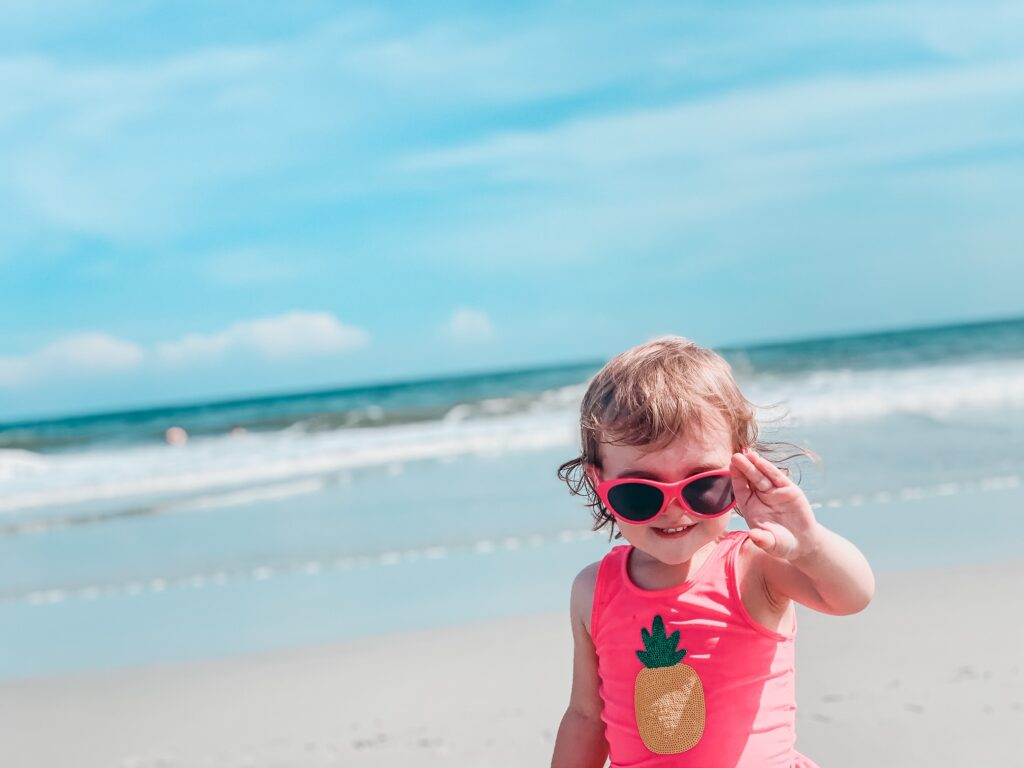 little girl on beach with sunglasses